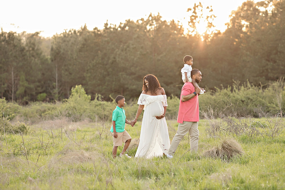 Image of an African American, family, with a pregnant mother, walking in an Atlanta field at sunset.
