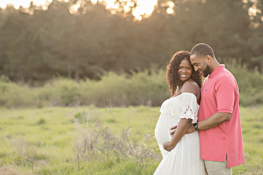 Image of a pregnant, African American woman, wearing a white, off the shoulder, dress, with buttons down the front, while her husband hugs her from behind and smiles down.