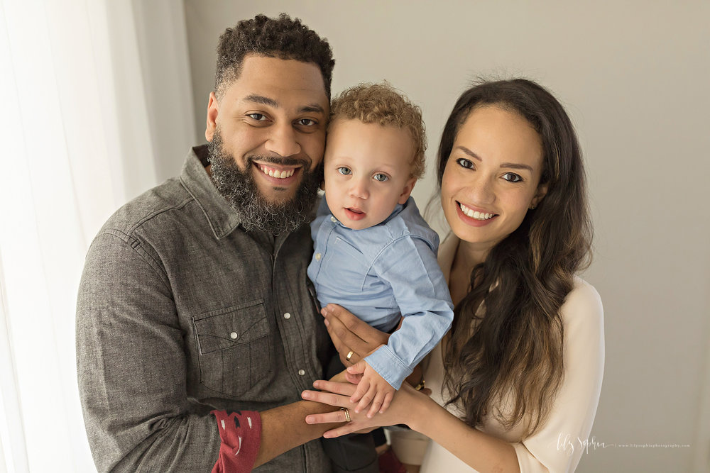 Image of parents holding their curly haired, blue eyed, baby boy and smiling for the camera.