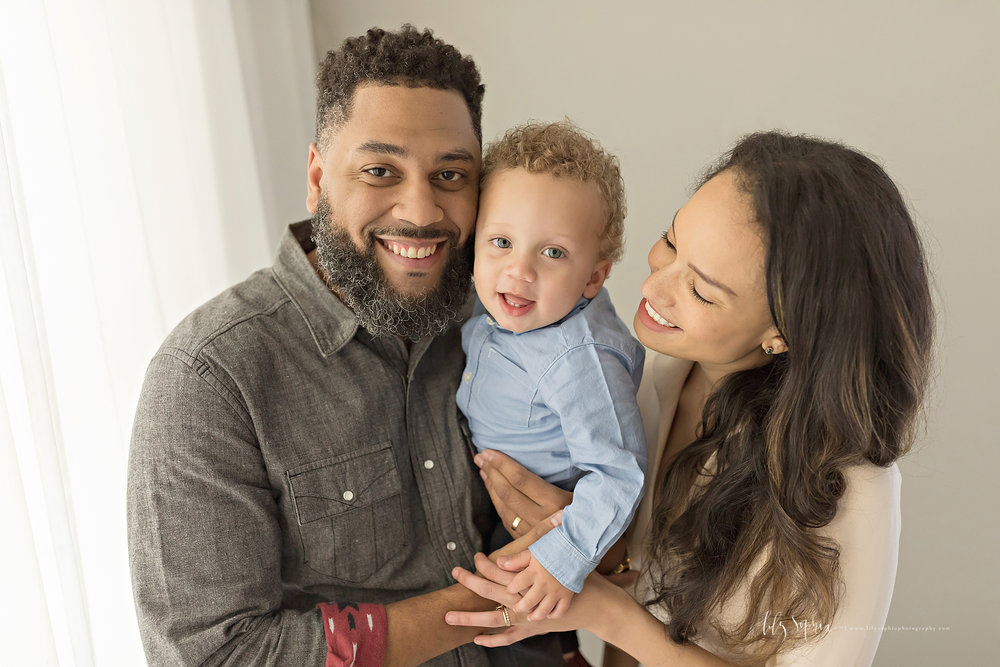 Image of an African American dad, holding his baby son in his arms with his wife looking on, smiling.