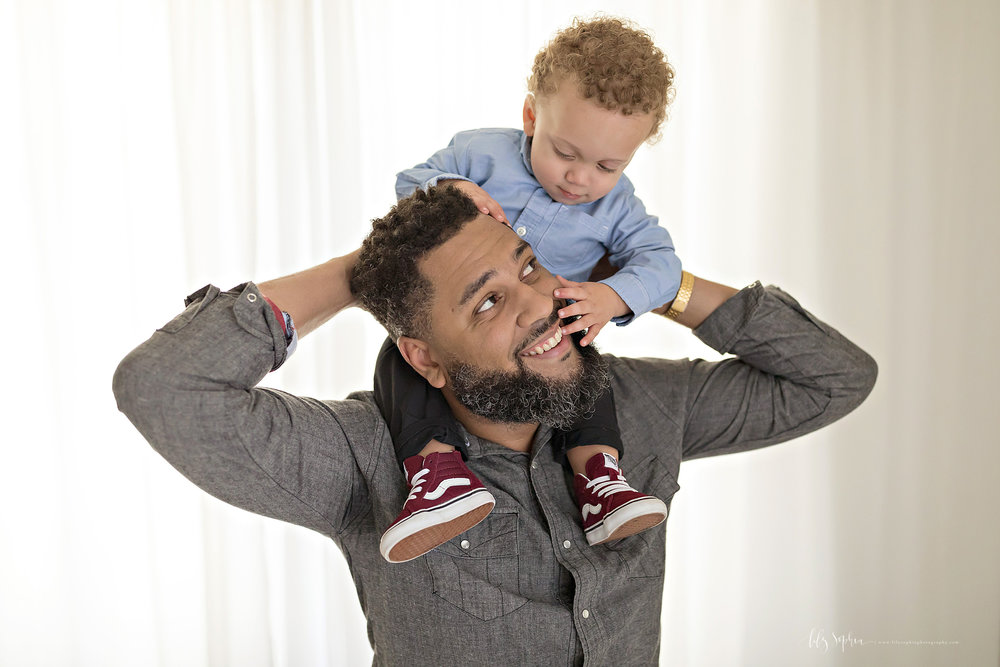 Image of an African American father, holding his son on his shoulders, smiling up at him, while his son looks down and has his hands on his dad's face.