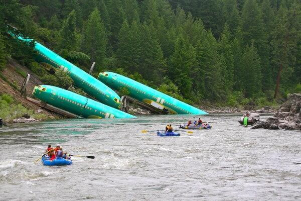 Several Boeing 737 fuselages lie in the Clark Fork River following the train derailment