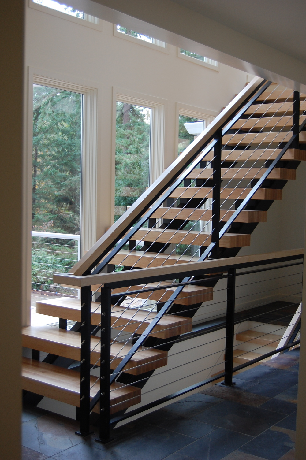 Painted steel staircase with 3 floors of continuous cable railing built out of solid flat bar.  Designed by MCM Construction