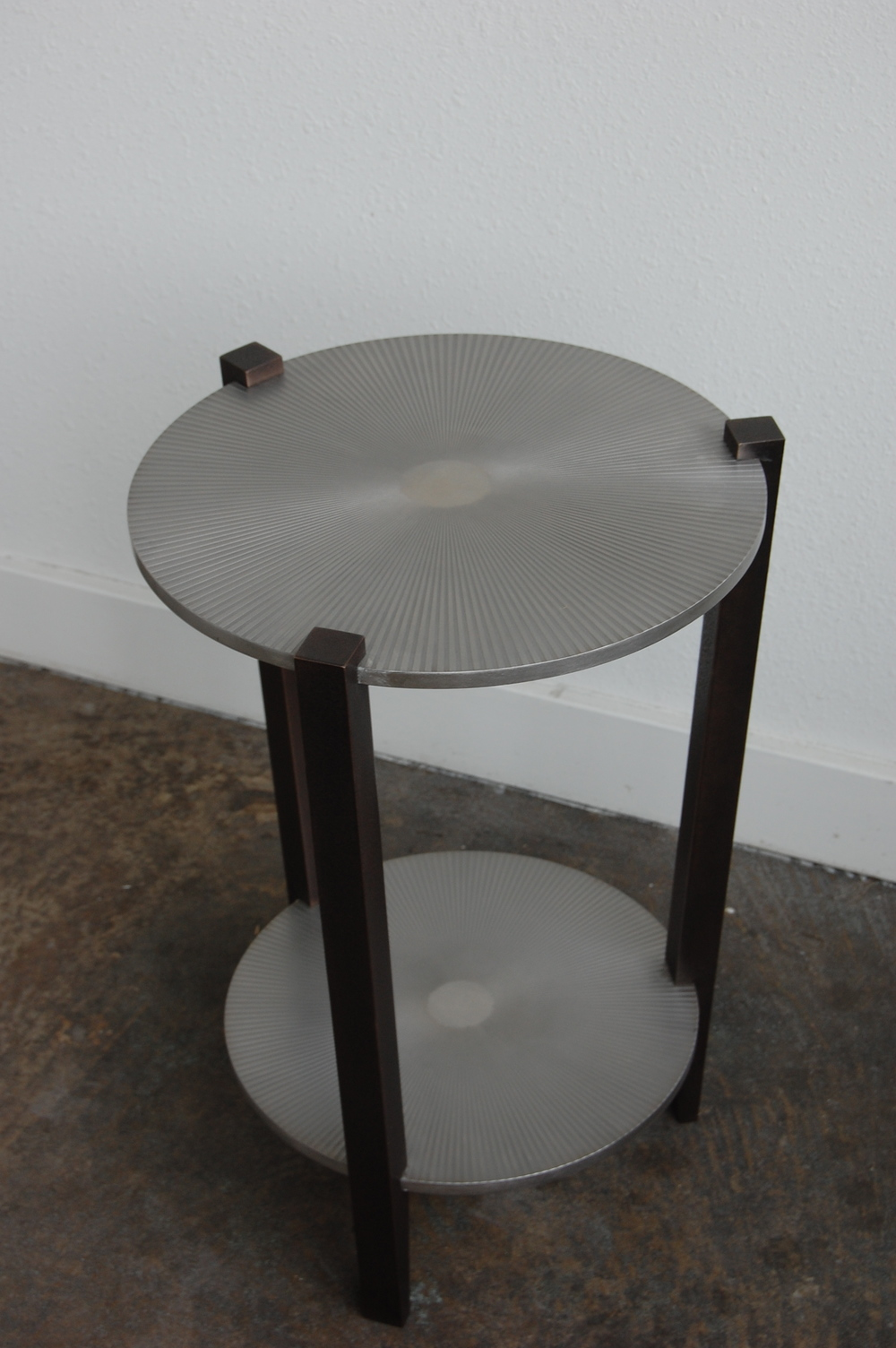 Stainless steel with starburst etched pattern. Legs are textured bronze.  Designed by Formed Objects