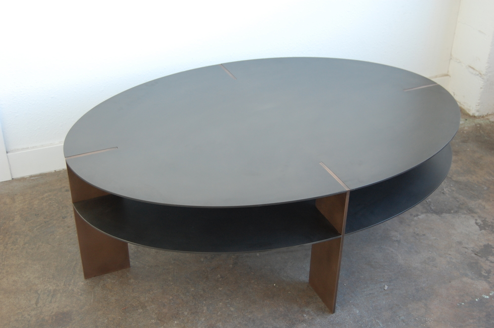 Hot rolled steel with textured bronze legs.  Designed by Hensel Design Studios