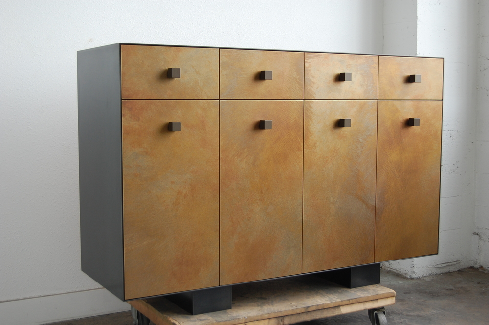 A wood cabinet that is clad in Hot Rolled Steel and brass sheet with patina.  Designed by Hensel Design Studios
