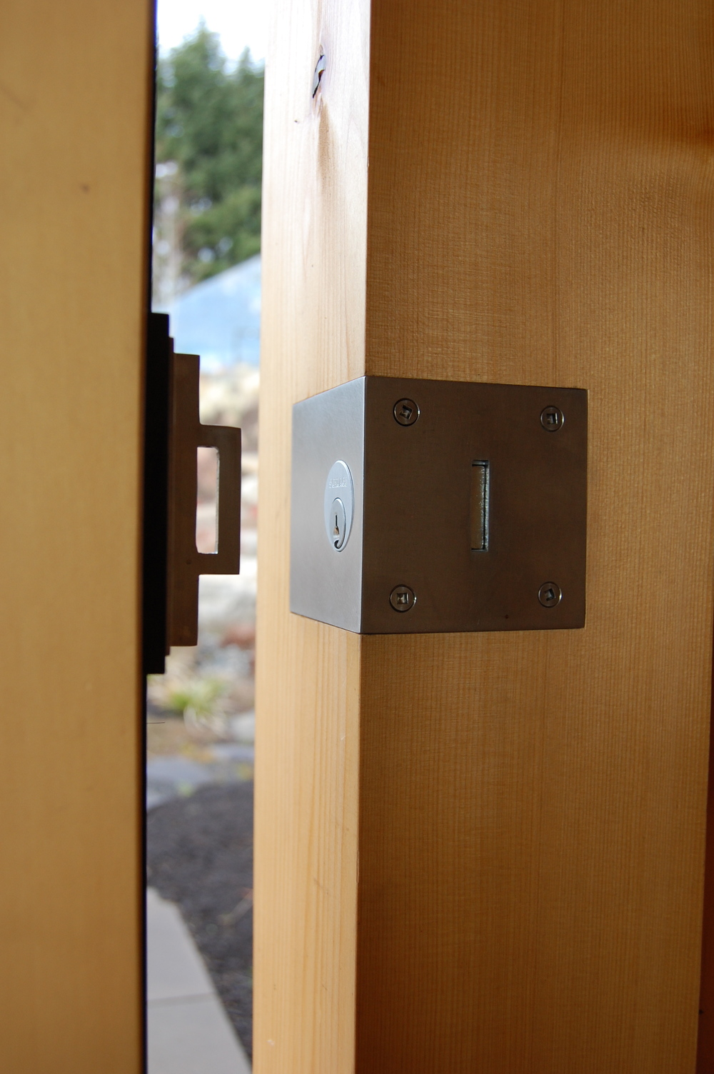 Stainless steel door lock.  Designed by Greenline Fine Woodworking