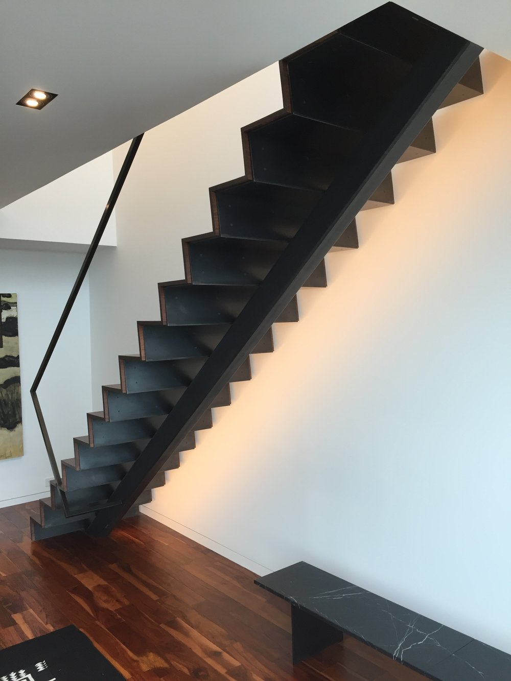 A folded steel staircase with a tube steel spine.  Designed by Paul McKean Architects