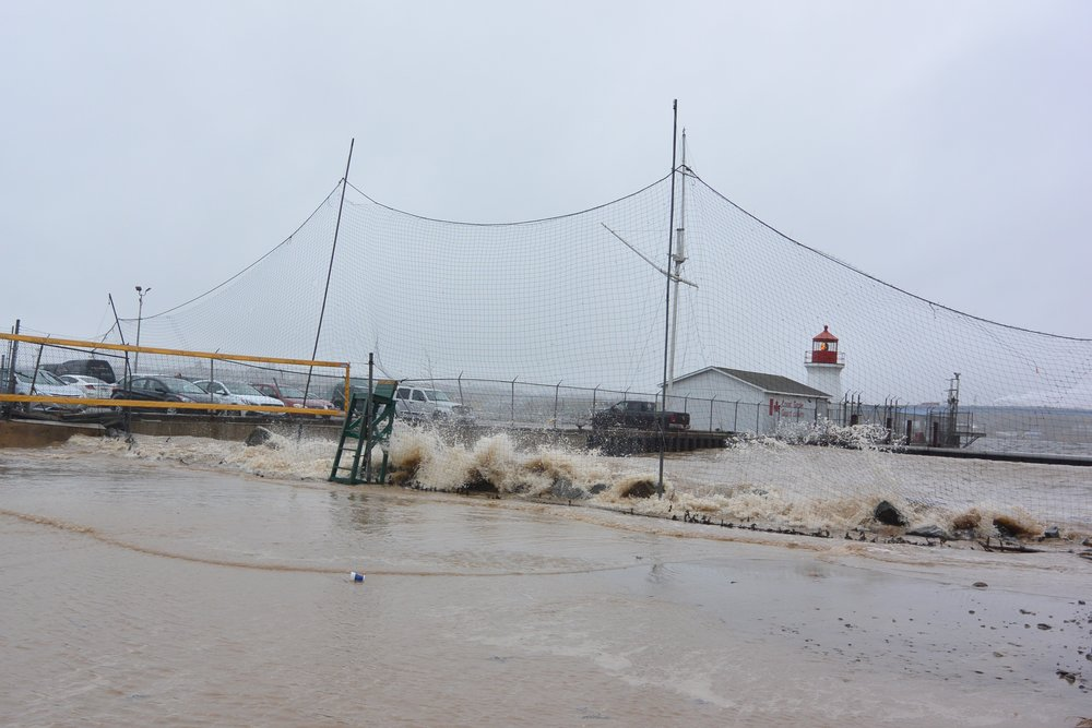 A combination of high tide and storm surge in Saint John on October 29, 2015 gave an indication of where coastal infrastructure is already at risk to flooding and erosion. This image shows waves crashing over the rocks and into the beach volleyball courts next to Loyalist Plaza. Coastal infrastructure will be at greater risk in the future due to sea level rise which will contribute to higher tide levels over the rest of this century and more frequent storm surges and extreme weather events.