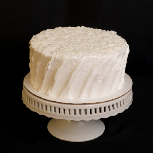 "Coconut  Two layers of coconut cake filled with vanilla butter cream and flaked coconut; topped with 7 minute frosting and shredded coconut.  6"" (serves 8): $28  