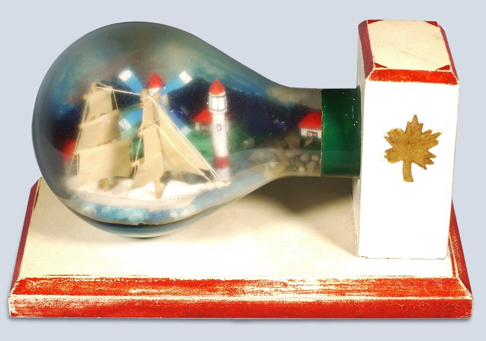 Ship in a Light Bulb, wood, glass, paint, mixed media, 19.7 x 9.9 x 11.3 cm, Second World War, Collection of Esplanade Arts & Heritage Centre Museum, Medicine Hat, Alberta. Photo: Courtesy of the Esplanade Arts & Heritage Centre