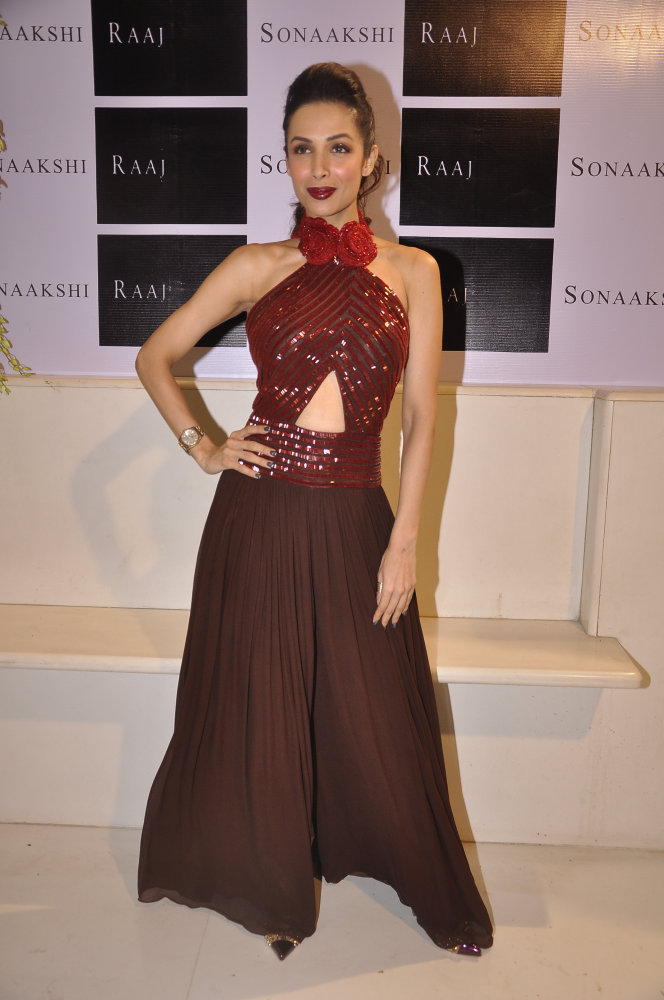 Malaika Arora Khan in a coffee brown and ruby red detailed halter palazzo jumper with ruby rose collar detailing.