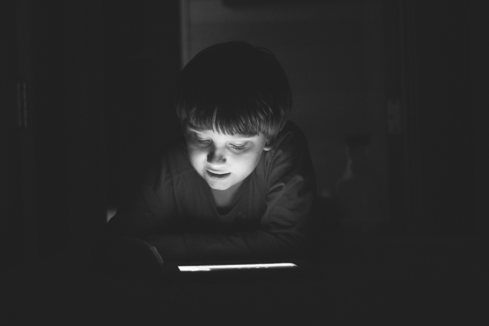My oldest playing on the iPad in the dark hallway in November of 2013 by Jenny Ryan of Amiabelle.