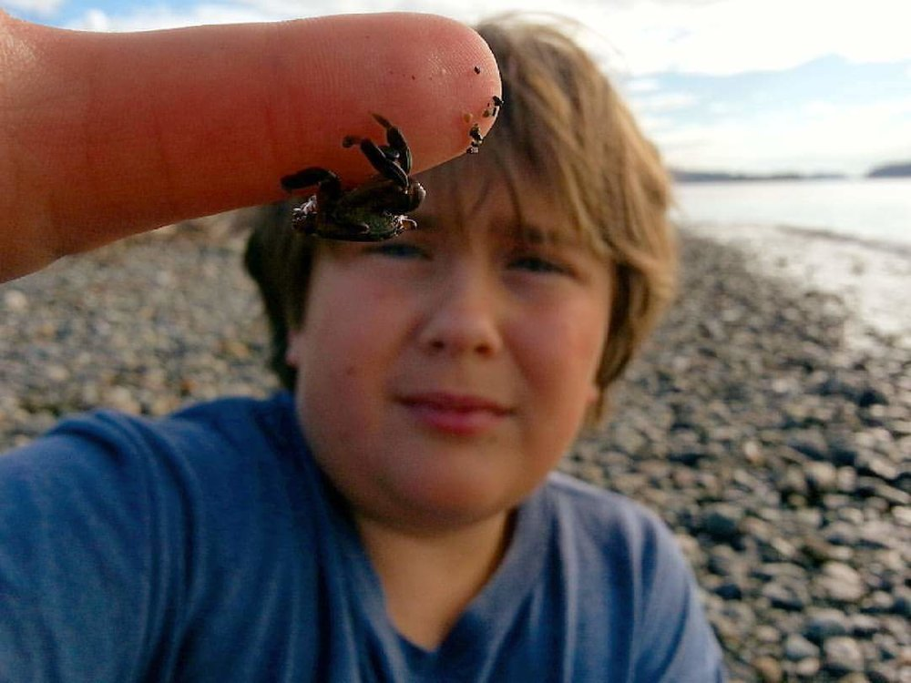 Show the people or the place, but focus on the point of the photo. My kid with a crab. Focus on the crab.