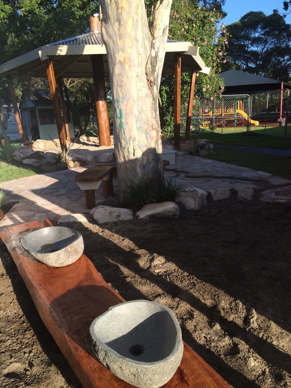 Looking back now from the Mud-pit  to the Water Course and arrive at the transformed Sand-Pit. Look at the beautiful stone bowl with drainage into the mud-pit and seating for adults and children alike