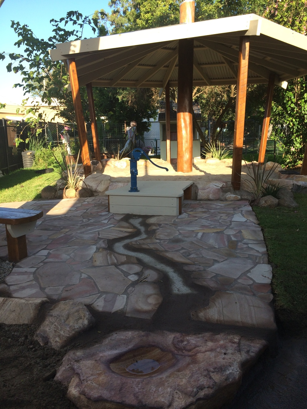 This Hand water Pump has a Under-Ground collection Tank that is connected to the existing Kindies Water Tank. Add easy to maintain crazy-pave Sandstone and Wellah  fun for all.