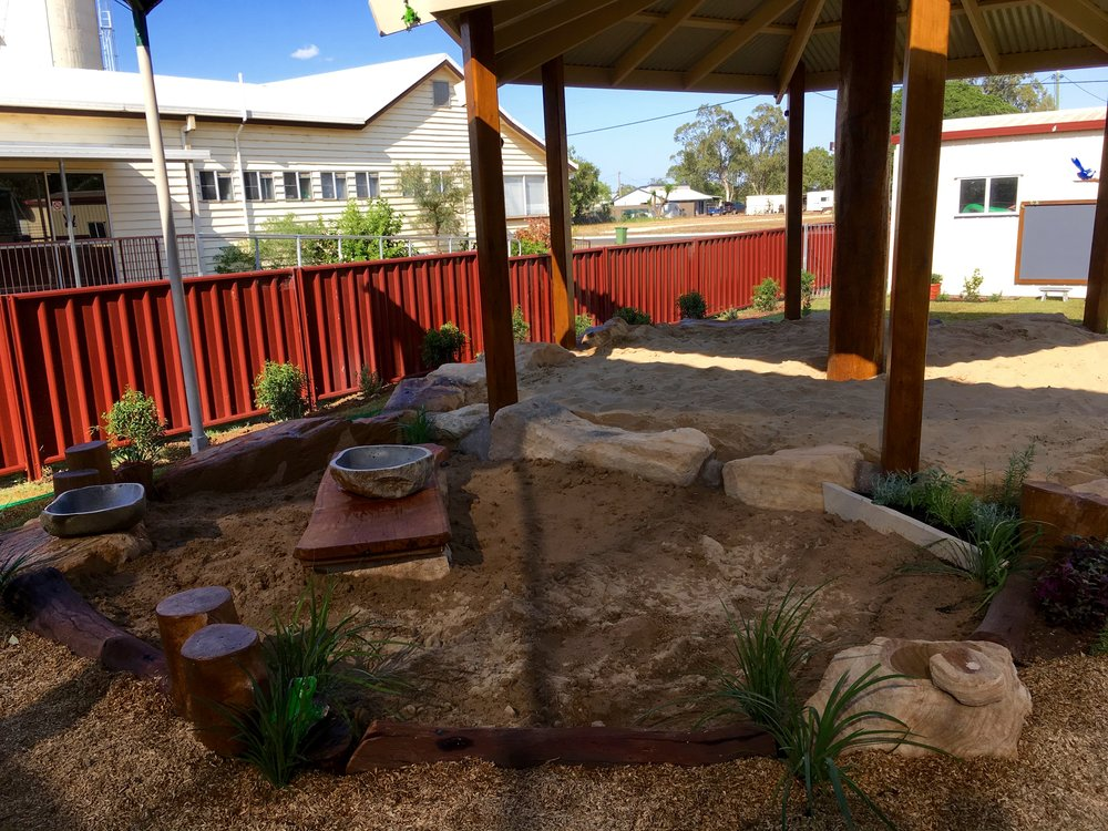 A Tree-house style Sand-pit roof with our signature sand-stone boulder surround connect to a new Mud kitchen with a herb garden and dogs and steppers keep it cool and natural. Fabulous for water play.