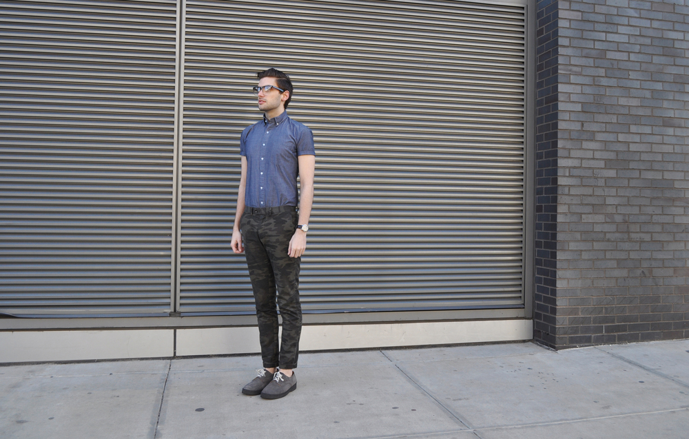 Today's chambray look: Commando Sometimes you have to get a little cheeky. A short sleeve chambray shirt works perfectly on its own or with a tie or bow tie. It's a great way to look polished in the Spring without all the extra layers. I paired mine with camo printed chinos (which can go south real quick if you're not careful. Go the opposite of Duck Dynasty with a polished shirt and shoes for a city-ready look. Camo will make you stand out, not blend in, and you want it to for all the right reasons.). The Mark McNairy shoes and thick glasses add a bit of wit to the look. What do you think?  Photo Credit: Michael Georgen American Apparel Chambray Shirt / Banana Republic Camo Chinos (Similar here and here) / Mark McNairy Shoes (Similar style here and here) / Burberry Watch