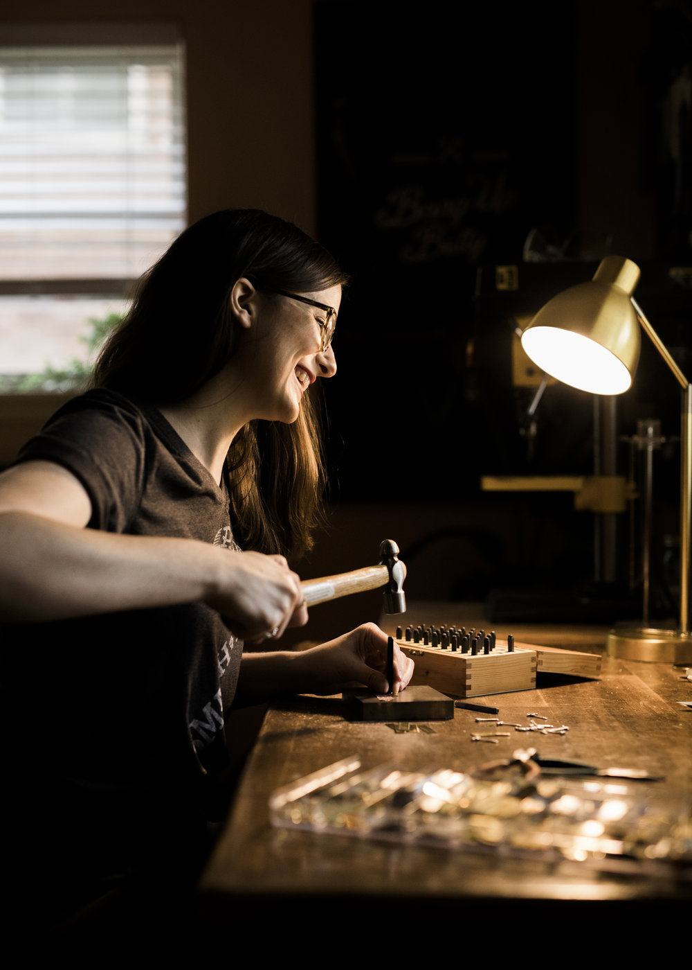 Arkansas jewelry maker Stacey Bowers at work in her home studio in North Little Rock stamping Bang-Up Betty jewelry.