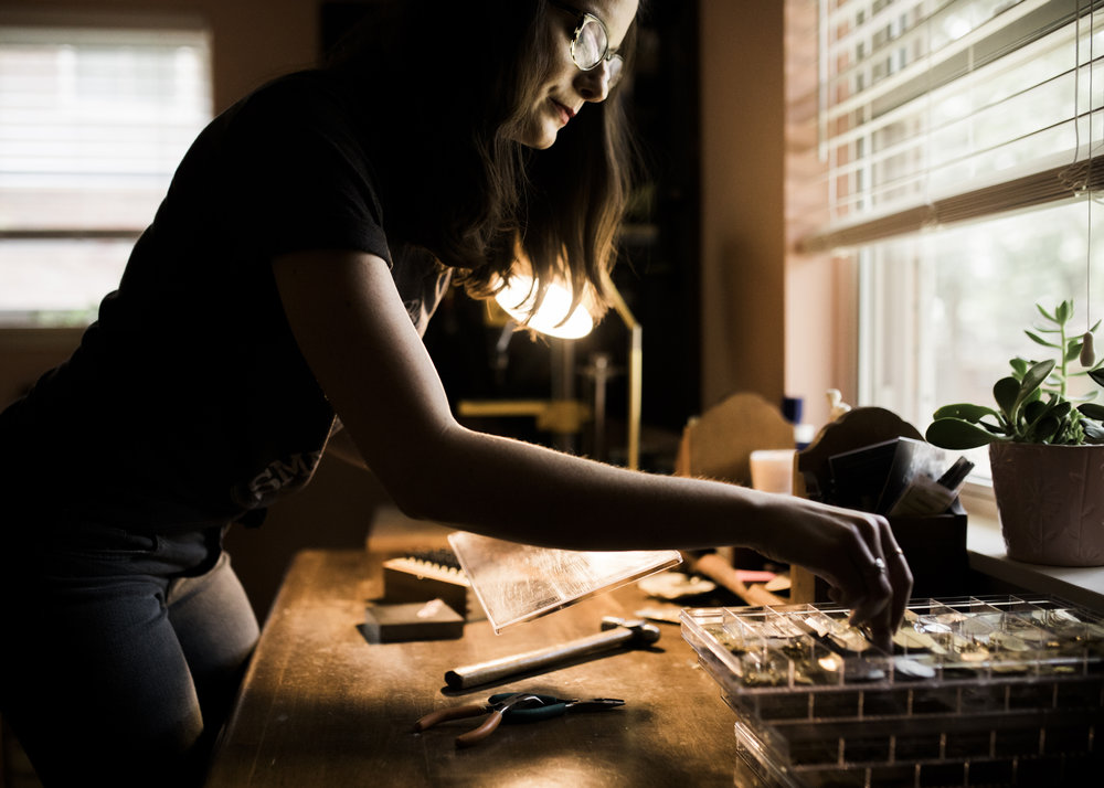 Jewelry designer Stacey Bowers selects a piece of brass to stamp with a hammer in her studio in North Little Rock, Arkansas.
