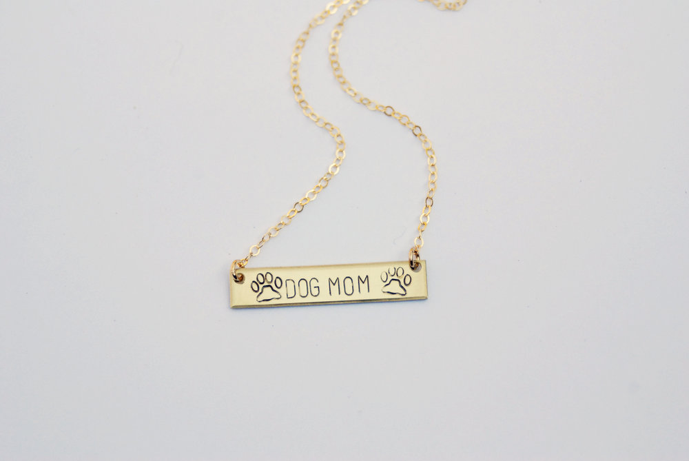 This stamped  Dog Mom Necklace  has the pawfect little paw print accents.