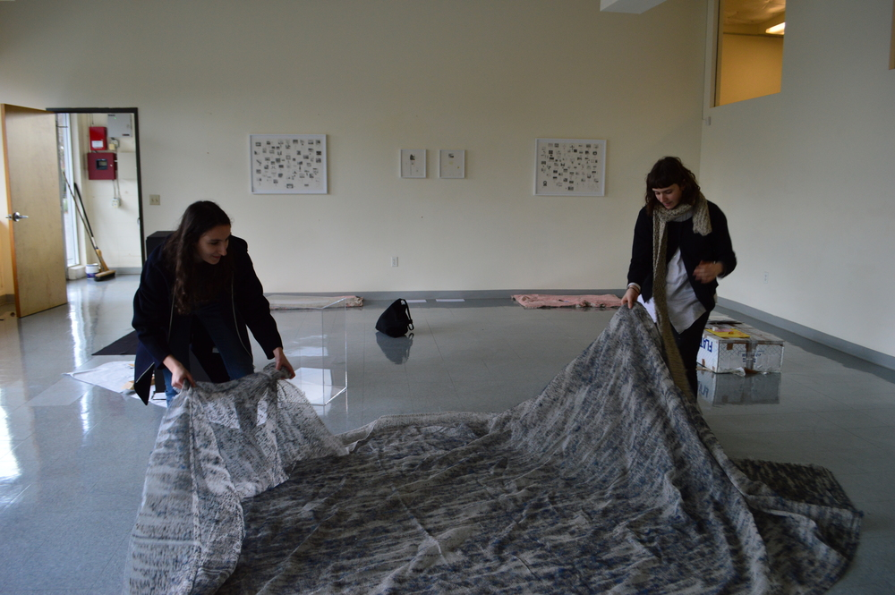 """Raw coordinators Lucy Weisner '16 and Jade Novarino '16 set up a piece of carpeting thats been picked apart by hand, revealing its fibrous skeleton."""