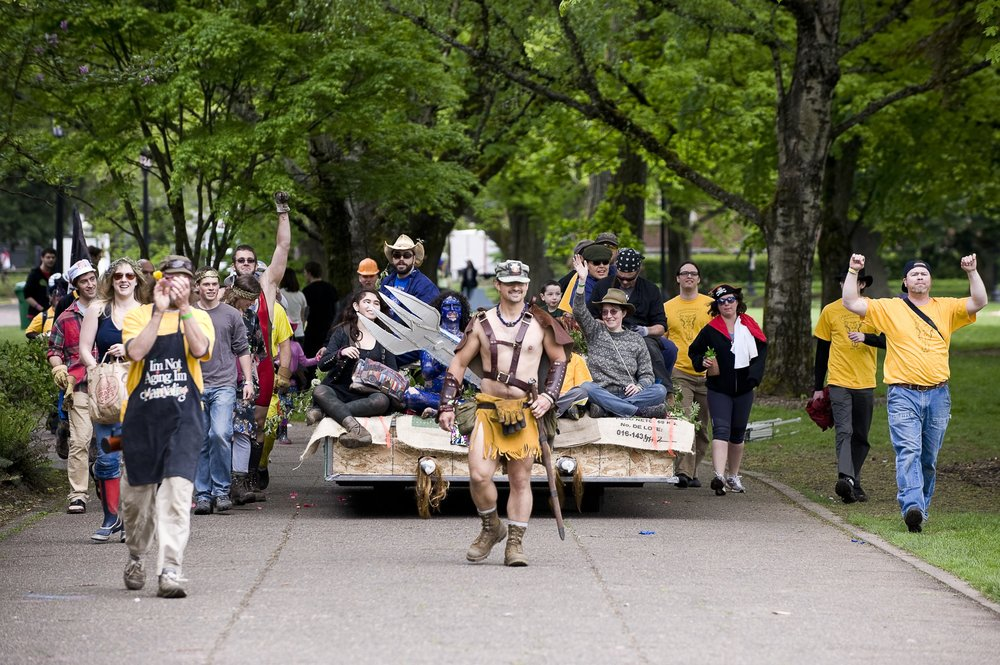 The alumni of Meatsmoke parade toward Sallyport with their float of non-vegan delicacies, picters in tow. Photo courtesy of Special Collections, Eric V. Hauser Memorial Library, Reed College.