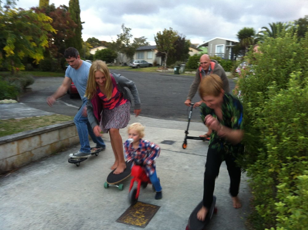 Joe racing the kids on skateboards at the BBQ.