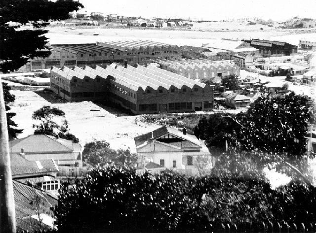 A photograph of wool stores in Ahuriri, Napier. Westshore can be seen across the water. Date post 3 February 1931.  Source