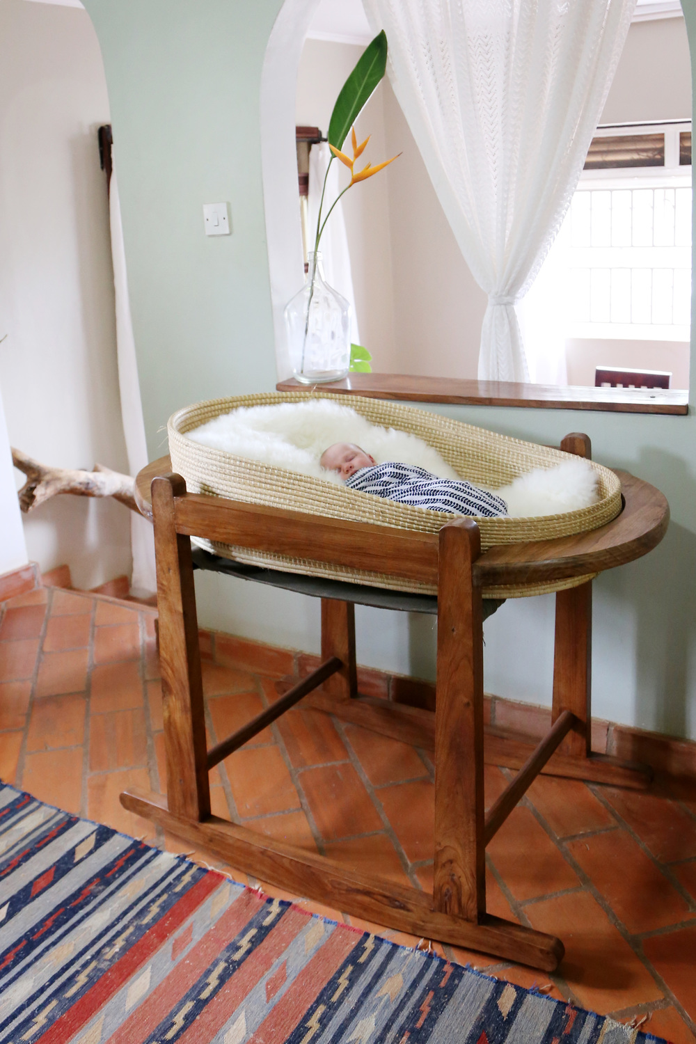 Bassinet stand made by a local carpenter and Moses basket woven in western Uganda.  Both are available at  Baby Lionheart.  Sheepskin rug from  Ecowool .