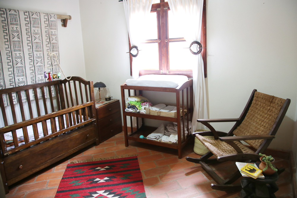 Crib, changing table, and rocking chair all made locally and bought second-hand.  Mudcloth wall hanging from  Mazmoon's Treasures.   Rug bought on a  trip to Jordan.