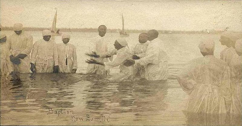 """Wade in the Water."" Postcard of a river baptism in New Bern, NC near the turn of the 20th Century. Original source: Wikimedia."