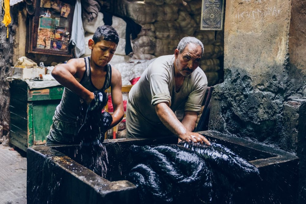 """Salama Mahmoud's dye workshop, where the cotton skeins are dunked in black ink from """"Alive With Artisans: Cairo's al-Darb al-Ahmar District"""" photography by Christopher Wilton-Steer. Link to text and photos below."""