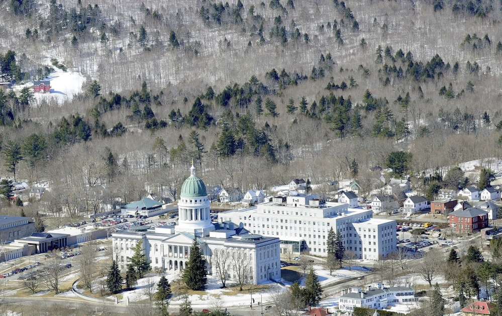 PROPOSED FOR CITY ACQUISITION: This aerial taken in late March shows Howard Hill, 164 wooded acres that serve as the scenic forested backdrop for the State House. Staff photo by Joe Phelan