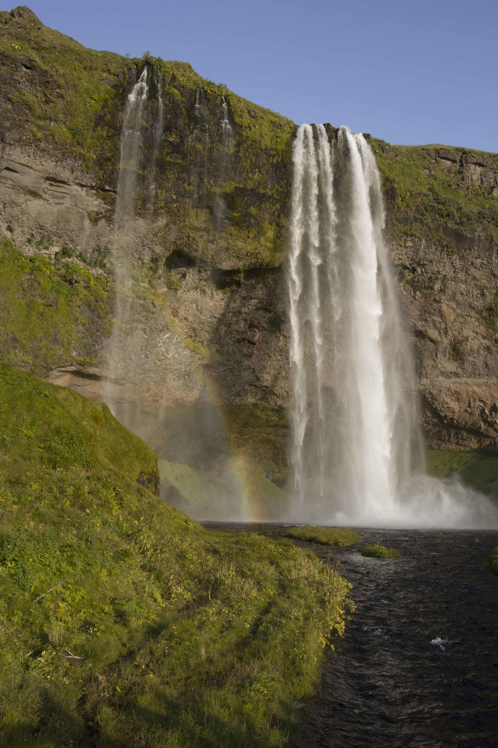 Rainbows at Seljalandsfoss campground. Now we see some crowds of tourists.  Love that you can walk behind this waterfall.