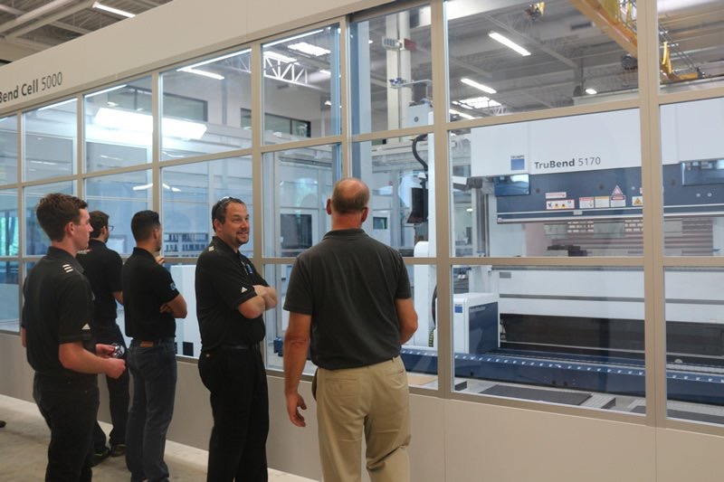 Freedom Autosport being shown a bending machine while at TRUMPF, Inc.