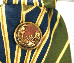 An example of a Victorian picture button designed in a floral motif using brass and wood.