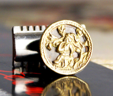 This Mag TAK is an upcycled Victorian brasspicture button from over a hundred years ago. It features a little fella blowing a horn