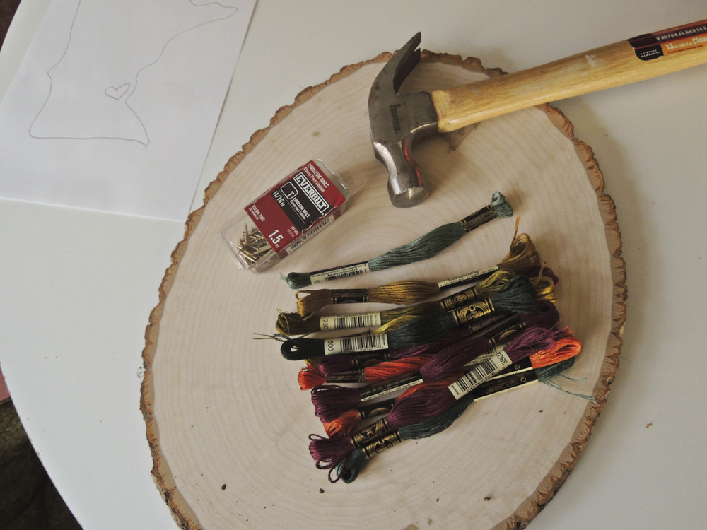 Wood circle, embroidery thread, linoleum nails, hammer and a drawing of Minnesota.