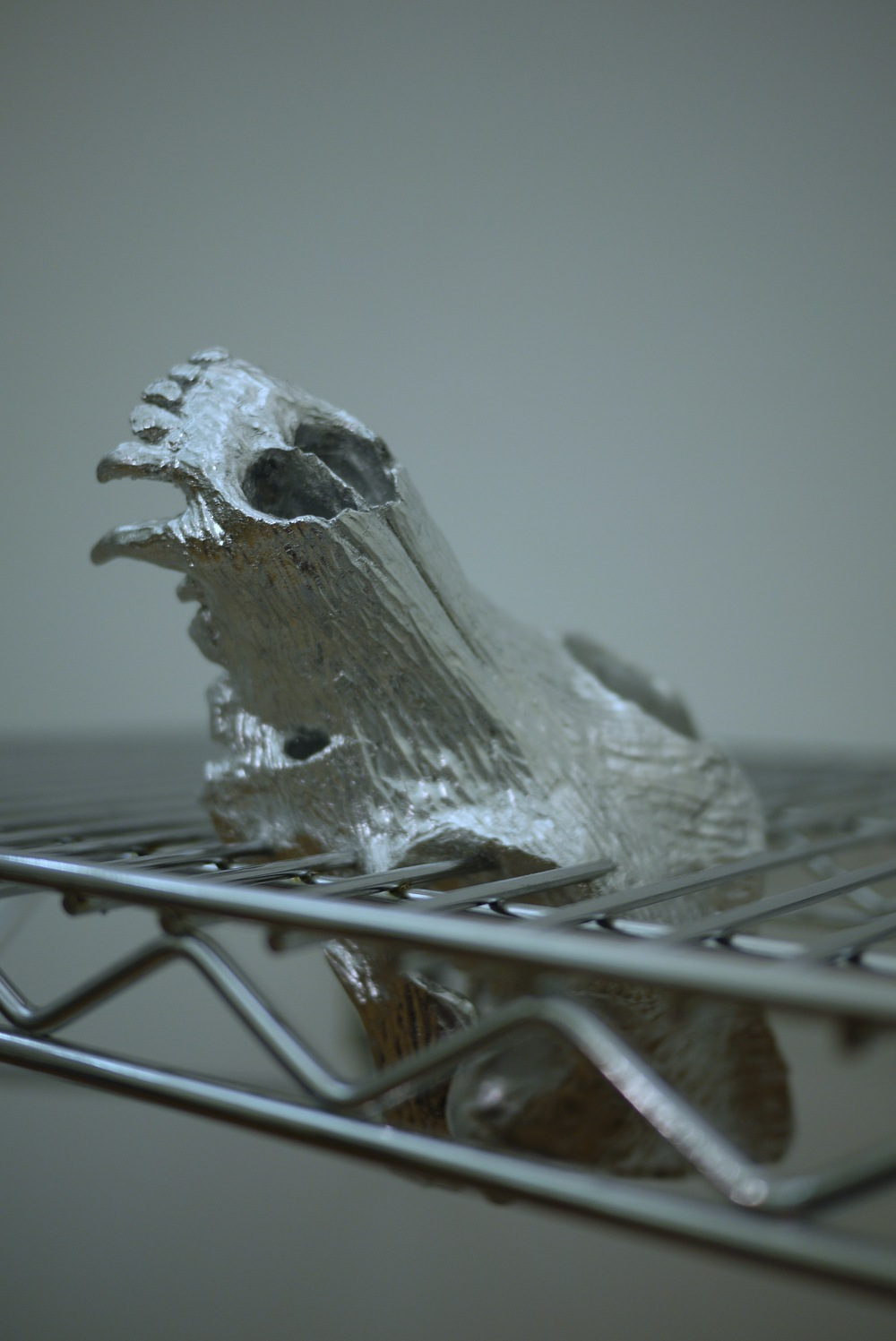 """It's not worth going on without a body, 2014,60""""x20""""x23, chrome wire shelf, bondo, silver leaf, magic sculpt, wire, paint"""