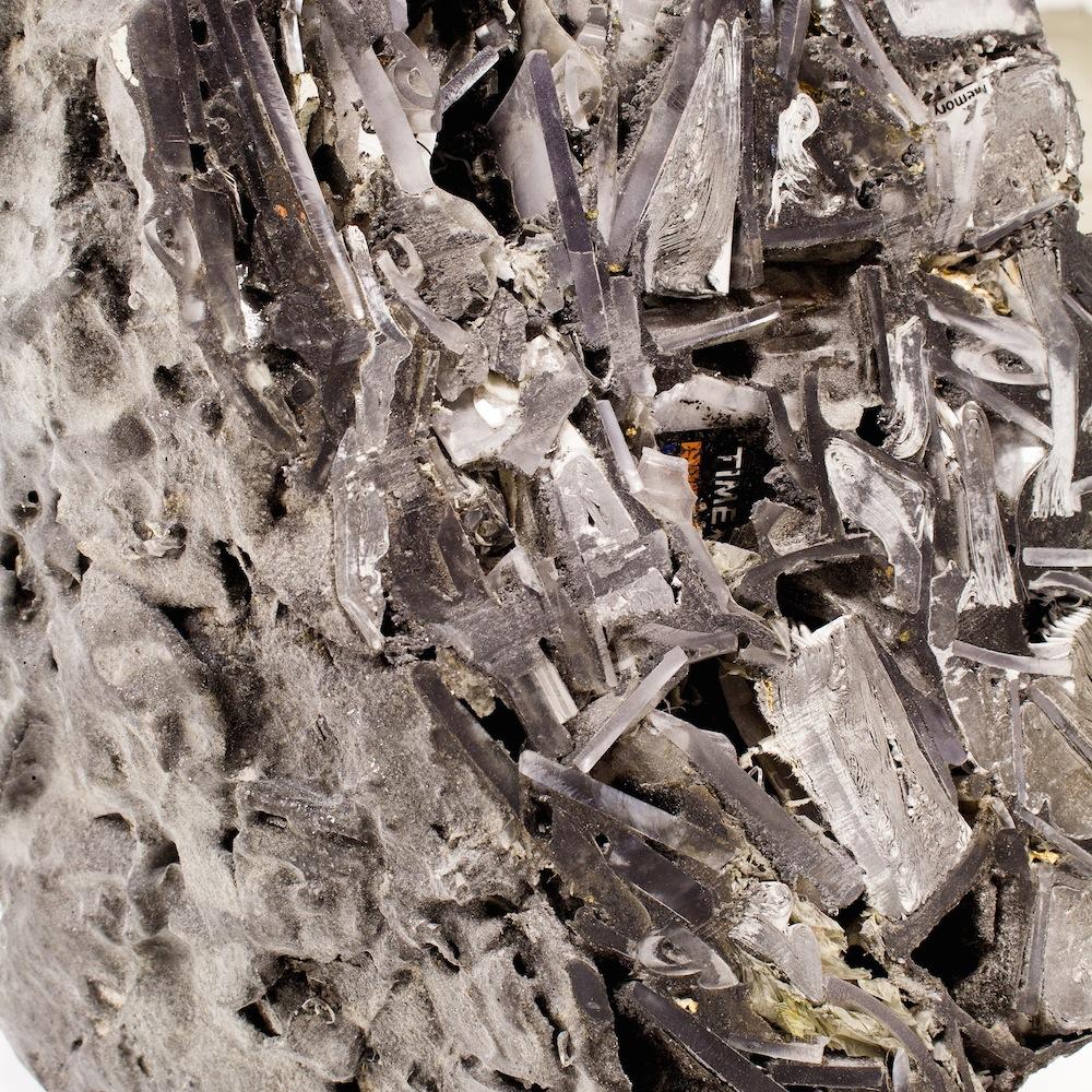"On the Beach,2015, 34""x34""x48"", plastic, resin, graphite, clay, sand, gold, aluminum, copper, chrome, nickel, glass, fossil gastropods, fossil shark teeth, foam, silica, wristwatch packaging, Motorola Razr, steel folding table"