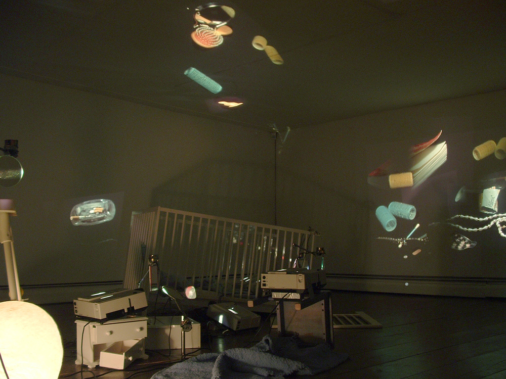 Eulalia Valldosera,  Still life (Provisional Living #3),  2000 Installation with 6 slide projectors, 8 hand mirrors set upon rotary motors, furniture of a child's room