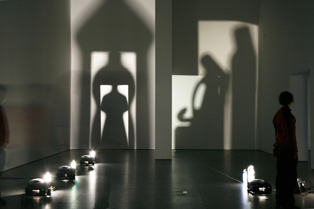 Eulalia Valldosera,  Envases el culto a la madre,  1996     Series of 4 light installations 1996 (detail)   1. Woman Seed.  3 slide projectors without slides; 3 bottles of detergent, books  2.   Trinity  2 slide projectors without slides; 3 bottles of detergent, mirror, books