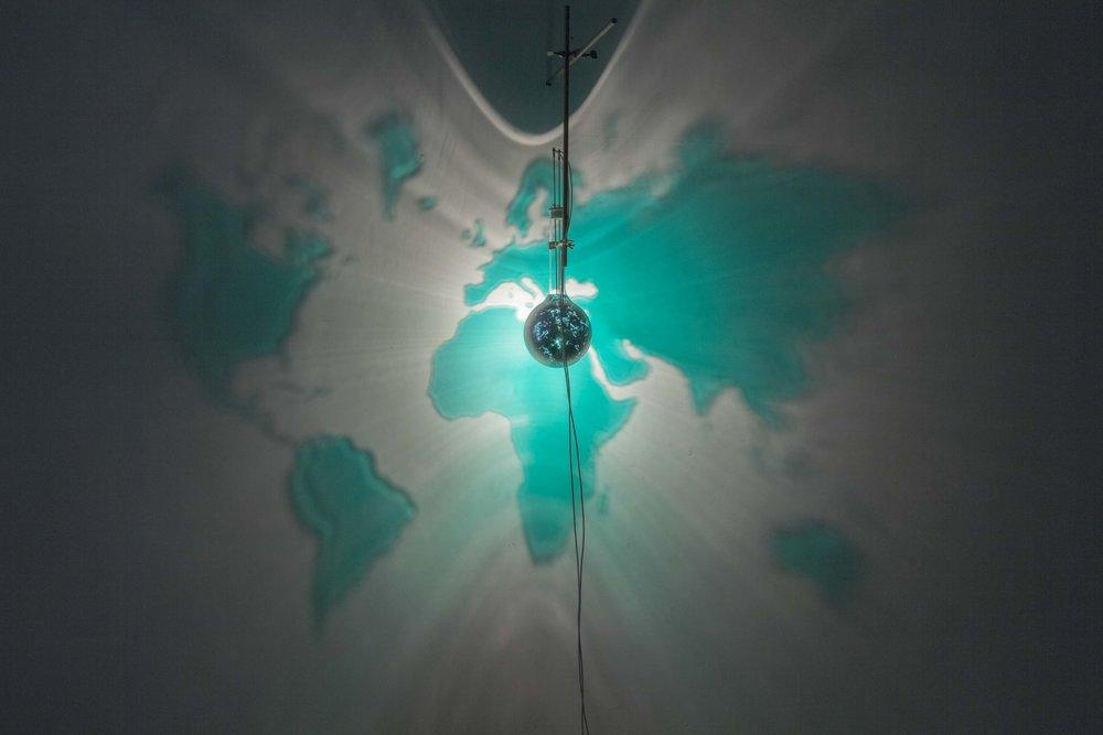Mondo Smeraldo , 2010, painted laboratory bottle, laboratory pliers, halogen lamp bottle diam. 16 cm, image 250x180 cm