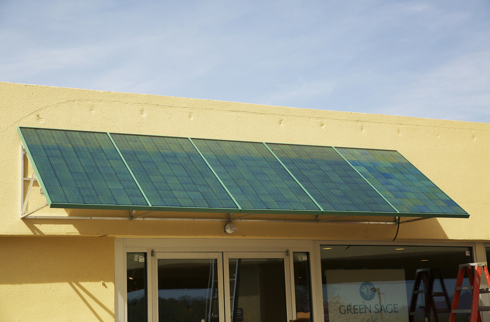 Photovoltaic solar panels act as an awning above the entrance door of Green Sage Cafe-Westgate.