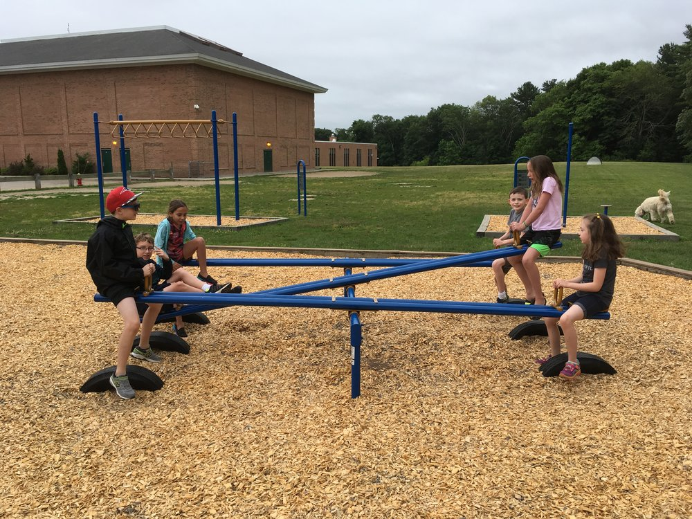 Six friends enjoy time at the see-saws. See-saws are not commonly seen on playgrounds anymore, so that makes this place even more fun.