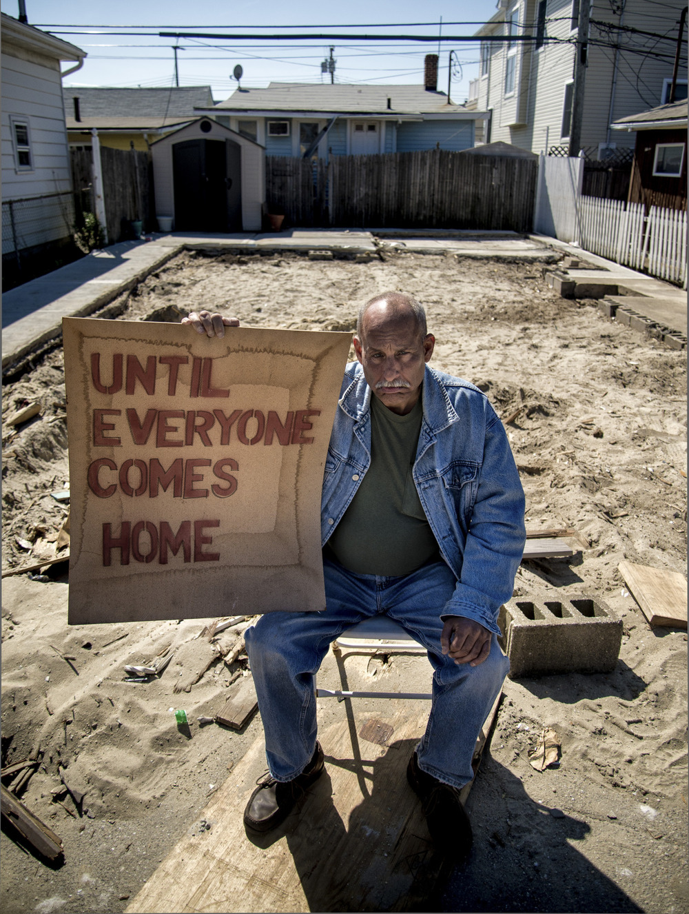 Rich Bartholomew sits on the plot of land where his West End, Long Beach home once stood, holding a sign drawn up by a neighbor for the community members.  Many of the Long Beach residents have felt exasperated at what they feel is the neglect and sheer lack of consideration shown by the town.   May 2 2013