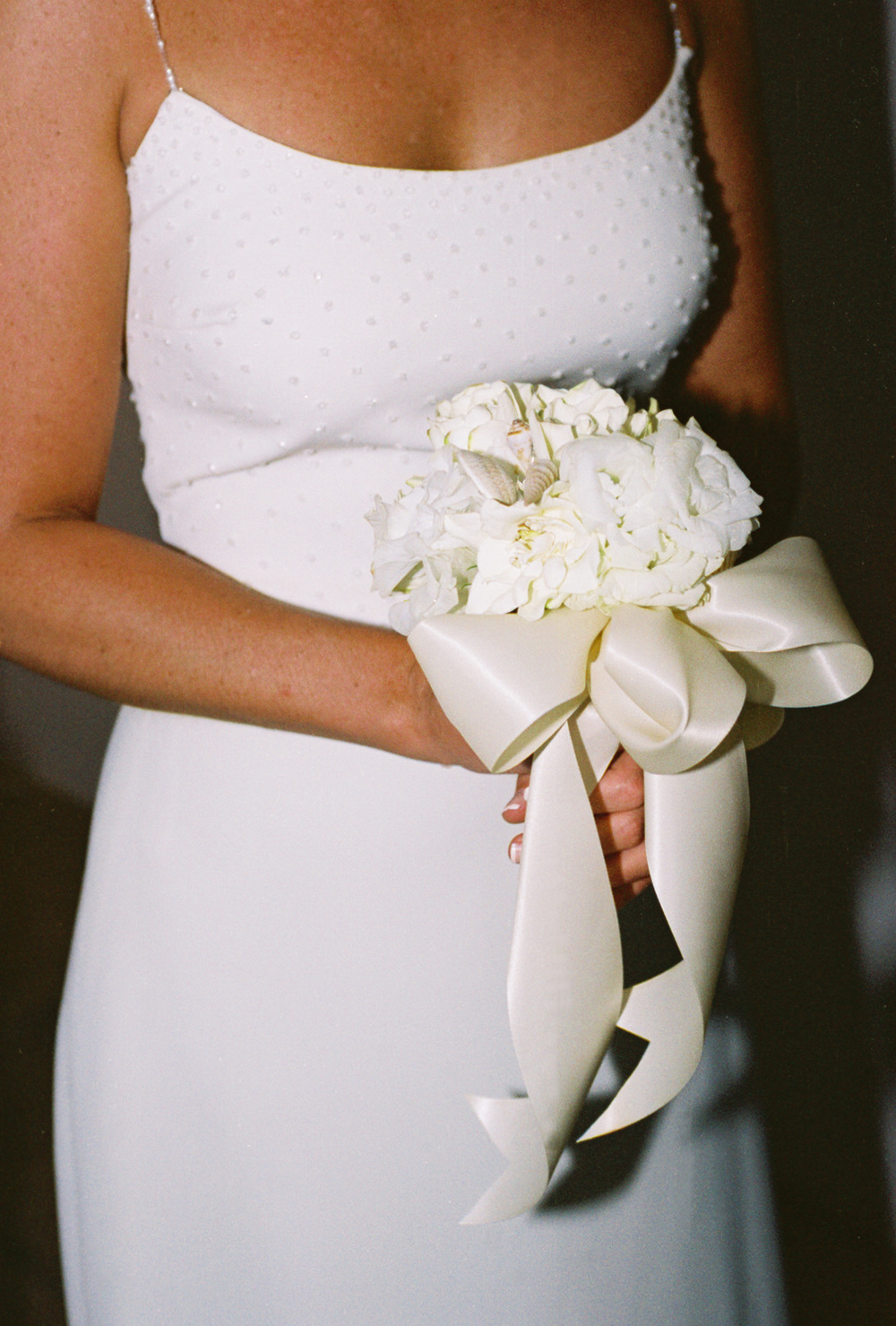 The bride carried a bouquet of gardenias tied with a white satin ribbon to compliment her pearl-studded wedding gown.
