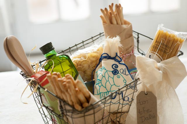 "For the pasta lover, start with a wire basket and add our hand-embroidered ""Cod"" design of Sal del Mar. Use your imagination with filling it with such gourmet items such as a bottle of extra virgin olive oil, breadsticks, and pasta. Then just tie on a ribbon and a tag."