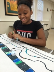 Girls STEAM club participant with Ozobot.
